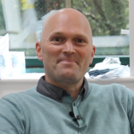 Photo of Chris Garlick wearing a light teal top smiling at the camera