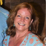 Photo of Liz Hill in a blue dress, smiling at the camera
