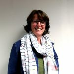 A picture of our Chief Executive, Mandy Evans smiling at the camera in front of a light background